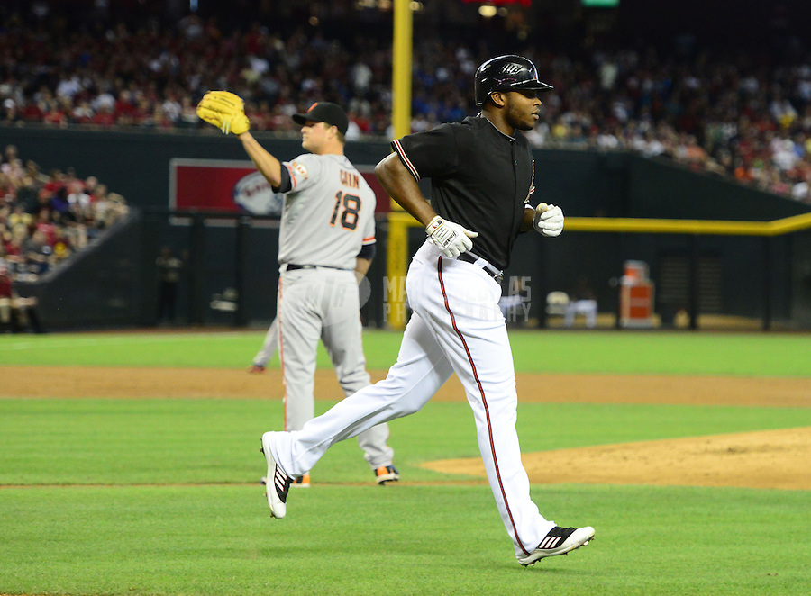 May 12, 2012; Phoenix, AZ, USA; Arizona Diamondbacks outfielder Justin Upton (right) heads to first base after being hit by a pitch from San Francisco Giants pitcher Matt Cain in the first inning at Chase Field. Mandatory Credit: Mark J. Rebilas-