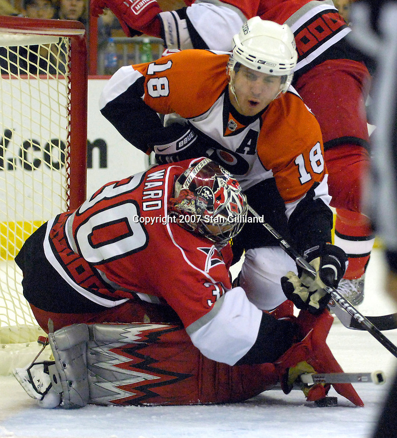 The Carolina Hurricanes' goalie Cam Ward makes a save as the Philadelphia Flyers' Mike Richards falls on him during their game Wednesday, Nov. 21, 2007 in Raleigh, NC. The Flyers won 6-3.