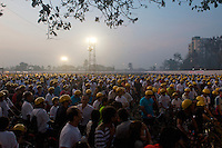 a sea of 7,500 participants illuminated under a single spotlight wait at dawn in the holding area at the start of the 2010 Mumbai Cyclothon citizen festival ride.  Reebok  provided the yellow hemat freebies for all participants. - Bombay/Mumbai - India