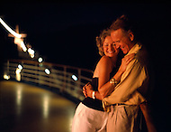 An older couple embraces on the deck of a cruise ship at sea