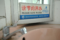 "A sign ""Please save water in a toilet.  The ten-year drought in northern China has meant that the reservoir is at just 25% of capacity. Beijing is pumping in water from southeren areas for the Olympics"