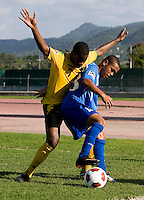 Romario Williams (7) of Jamaica tries to take the ball away from Carlos Andrade (18) of Honduras during the quarterfinals of the CONCACAF Men's Under 17 Championship at Catherine Hall Stadium in Montego Bay, Jamaica. Jamaica defeated Honduras, 2-1.