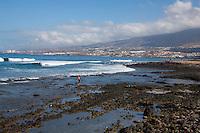 Lone figure walking along stoney beach, Playa de Las Americas,Tenerife, Canary Islands