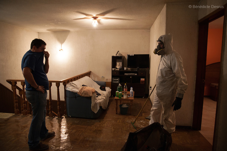 """Donovan, pictured with his client, after completing a forensic cleaning in Iztacalco, Mexico on October 16, 2015. The decomposed body of a man in his 60s was found in his bedroom a number of days after he died of a heart attack – although the deceased's own family members were unsure exactly how long he had been there. The victim's family remarked that the police had made unfounded insinuations against them, and had sought bribes. As a result they found Donovan's discretion and professionalism to be a welcome contrast. Donovan Tavera, 43, is the director of """"Limpieza Forense México"""", the country's first and so far the only government-accredited forensic cleaning company. Since 2000, Tavera, a self-taught forensic technician, and his family have offered services to clean up homicides, unattended death, suicides, the homes of compulsive hoarders and houses destroyed by fire or flooding. Despite rising violence that has left 70,000 people dead and 23,000 disappeared since 2006, Mexico has only one certified forensic cleaner. As a consequence, the biological hazards associated with crime scenes are going unchecked all around the country. Photo by Bénédicte Desrus"""