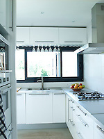 Every inch of space is used in the compact kitchen and an ingenious storage system for glasses has been installed under the wall cupboards