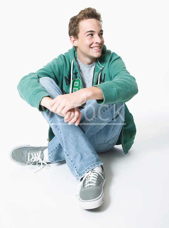 Teenage boy sitting cross-legged