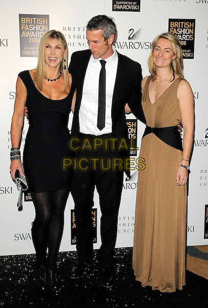 SHARRON DAVIES, MARC FOSTER & GUEST .Inside arrivals at the British Fashion Awards 2008 held at The Lawrence Hall in London, England. UK, .November 25th 2008.full length black dress tights ankle boots bracelets looking down cleavage funny long brown sharon .CAP/CAN.©Can Nguyen/Capital Pictures.