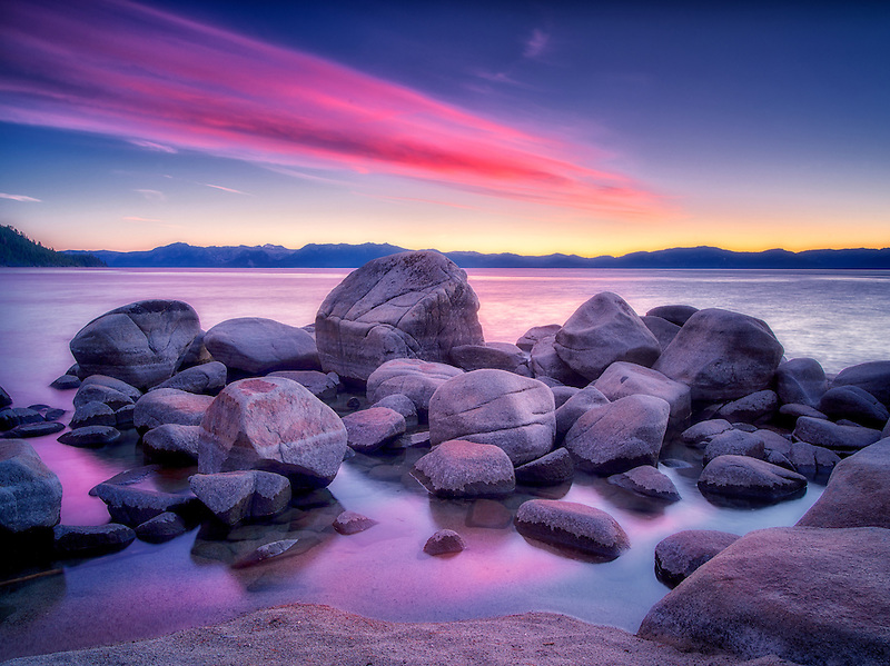 Boulder rocks and sunset on shoreline of Chimney Beach. Lake Tahoe, Nevada