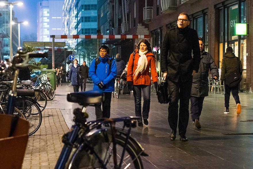 Nederland, Den Haag, 4 dec 2013<br /> Turfmarkt in de avond. Forensen lopen naar het station. Veel ambtenaren en andere medewerkers van de kantoren in dit gebied gaan met de trein naar huis<br /> Foto: (c) Michiel Wijnbergh