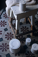 Ornamental porcelain replicas of tin cans are grouped on a tiled floor beside a painted stool