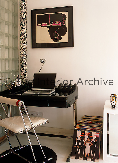 A laptop sits on a 70's preform black plastic desk with a pile of period records on the floor .