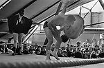Tag wrestling in Pat McKeowen's fairground travellers boxing booth show, on The Hill, at the annual Derby horse race Epsom Down, Surrey, England 1969.<br /> Jack Turner ( beneath shoulder of man being thrown,Jack is looking up )  who ran the fights at Pat McKeowen's  boxing booth. 1960s UK.