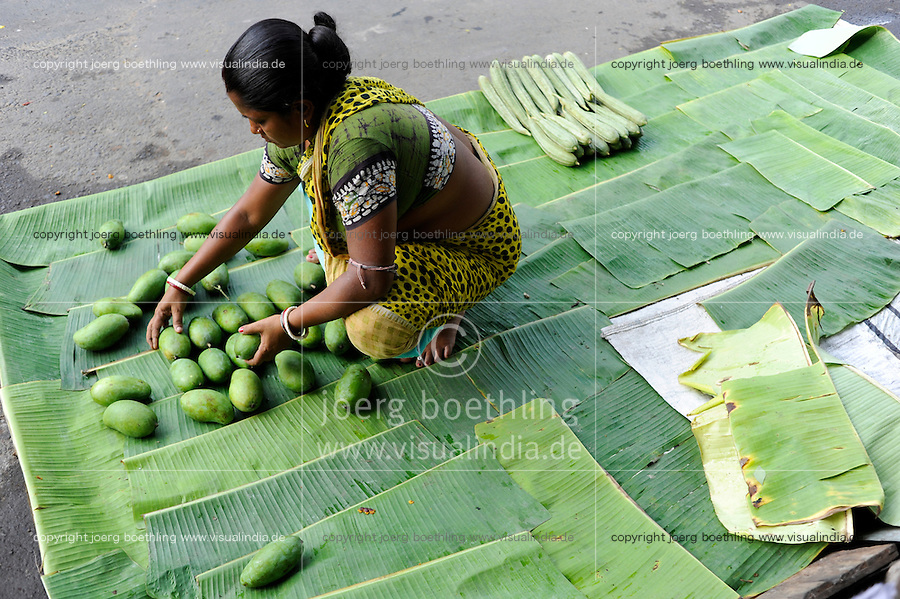 INDIA Calcutta, woman sell mango on the road / INDIEN Kalkutta, Frau sortiert Mango auf Bananenblatt fuer Strassenverkauf