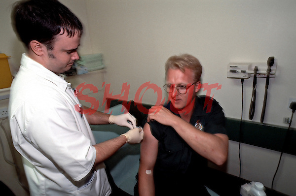 Nurse injecting a paramedic with a intramuscular tetanus injection as part of a course of treatment after he was cut whilst dealing with a HIV infected casualty. The paramedic was rushed into the crash room of an accident and emergency department.