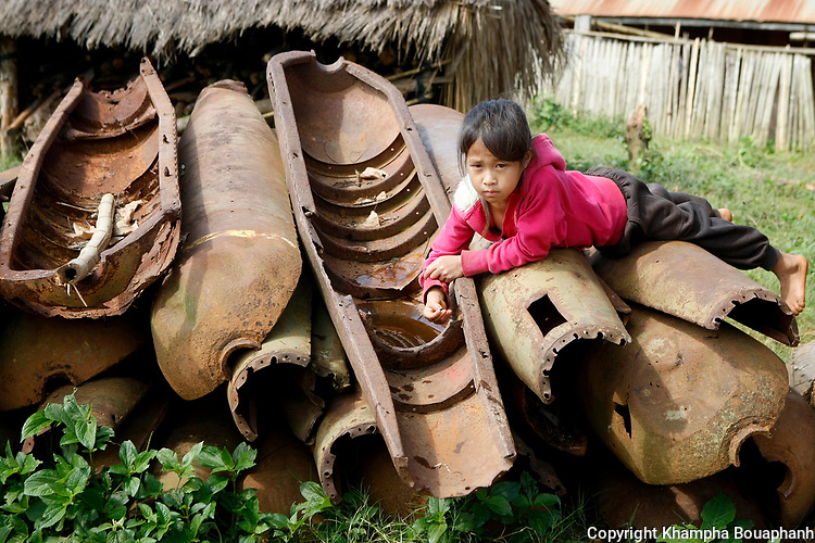A girl plays on top of a pile of bomb casings in Ban Na Khampheng in Xieng Khoung Province, Laos on Thursday, July 9, 2015. (photo by Khampha Bouaphanh)