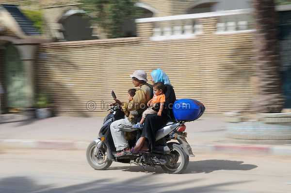 Africa, Tunisia, Tozeur. Tunisian family of father, mother and two children on moped. --- No releases available, but releases may not be needed for certain uses. Automotive trademarks are the property of the trademark holder, authorization may be needed for some uses.