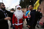 A Palestinian man dressed as Santa Clause takes part during a rally marking the fifty-four anniversary of the creation of the political party, in Gaza city on December 31, 2018. Photo by Ashraf Amra