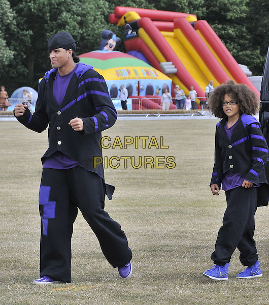 ASHLEY BANJO & PERRI LUC KIELY of Diversity .At the Duke of Essex Polo Trophy, Gaynes Park, Coopersale, Epping, Essex, England, UK,  17th July 2010..full length black purple suit outfit costume trousers baggy jacket hat cap walking trainers glasses .CAP/CAN.©Can Nguyen/Capital Pictures.