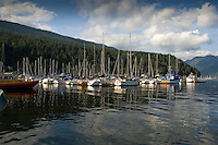 Boats moored at jetty with mountains and the trees of the Cove forest in the background. Deep Cove, Burrard Inlet, Vancouver, British Columbia, Canada.