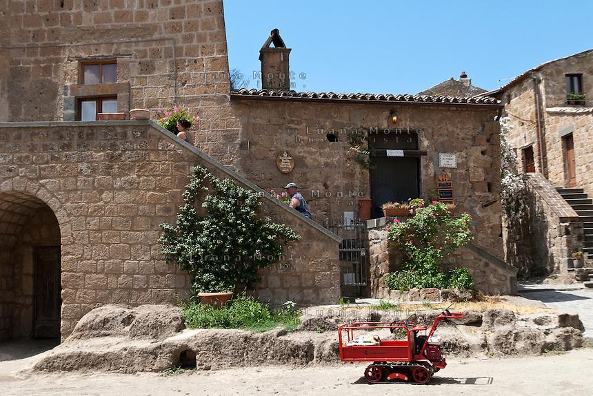 Civita di Bagnoregio. Il trasporto degli oggetti ingombranti a Civita può essere effettuato solo tramite piccoli trattori (come quello in primo piano) o motorini e ape car, poichè l'unica strada di accesso al borgo è quasi esclusivamente pedonale.