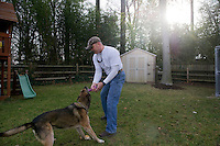 UNITED STATES - DECEMBER 12: K9 Technician Shawn Haynes plays with Hawk while off duty in his backyard at his home in Maryland. Hawk was his previous working dog, and he adopted him in 2011 after he retired from his decade-long career.