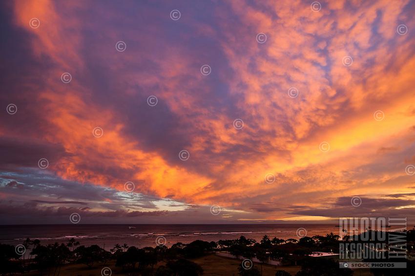 An epic sunset includes orange and pink clouds cascading across the sky over Ala Moana Beach on O'ahu.