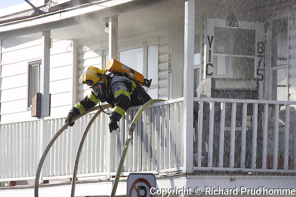A fireman passes water hoses over gallery at a building fire in Sainte-Beatrix