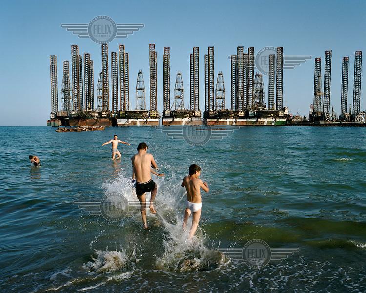 Boys splash in the Caspian Sea, in the shadow of oil rigs at Sixov beach in Baku.