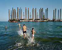 Boys splash in the Caspian Sea, in the shadow of oil rigs at Sixov beach in Baku.