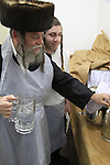 Matzah baking ahead of the Seder meal at the Hasidic Premishlan congrgation, the water for the dough making