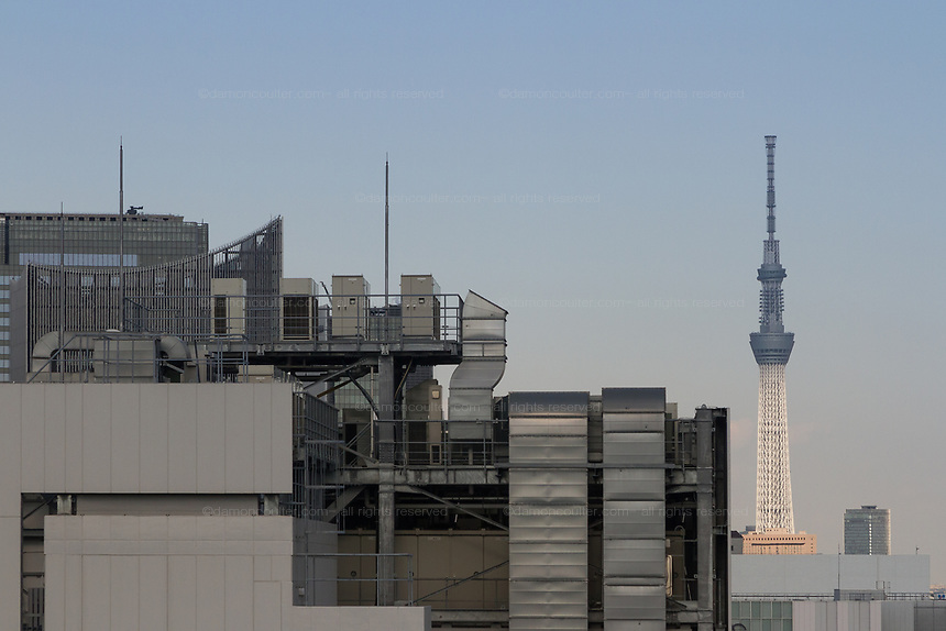 Shadows covers the top half of Tokyo Skytrre. Seen across rooftops in  Ginza, Tokyo, Japan. Wednesday February 5th 2020