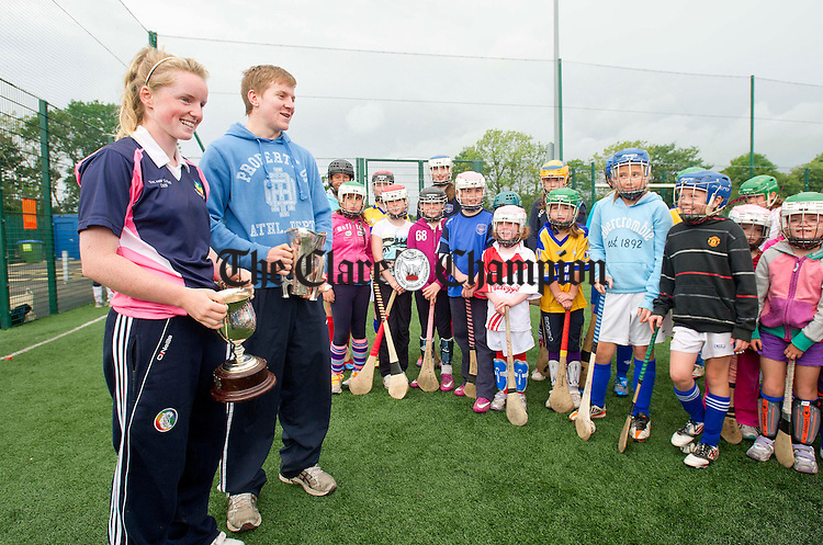 Naomi Carroll, Irish hockey player and member of the Clare senior camogie panel, and Paudge Collins, Clare U-21 hurler, arrive at Parteen GAA's Juvenile Hurling and Camogie Camp with the Munster U-21 hurling and senior camogie trophies. Photograph by Declan Monaghan