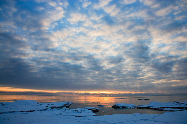 Sunrise light on cloud formations and ice formations in Lake Michigan at Newport State Park; Door County, WI