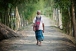 A man walks through West Fasura, a village on an island in the Brahmaputra River in northern Bangladesh.