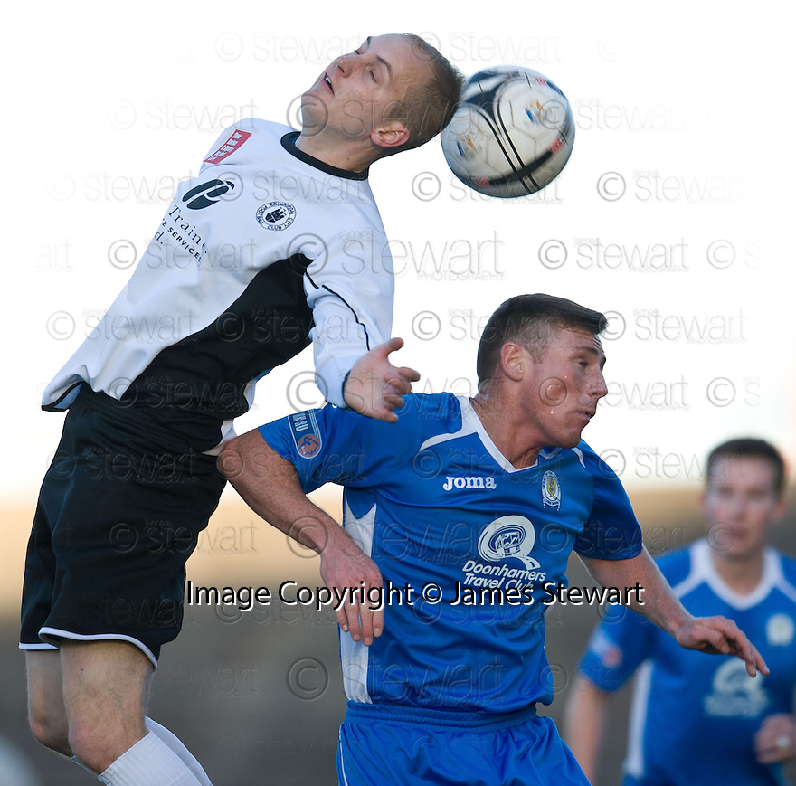 City's Andy Howat and Queen of the South's Chris Mitchell challenge for the ball ...