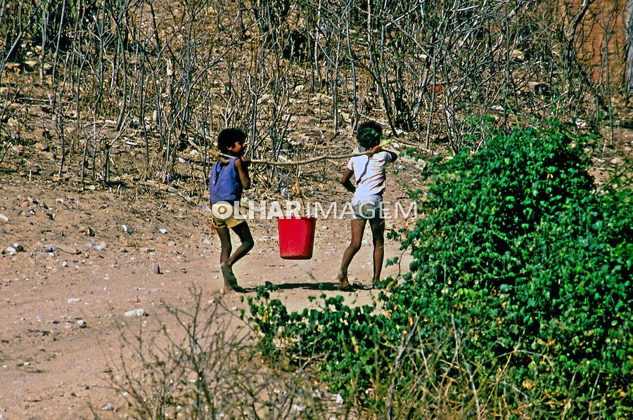 Crianças tranportam água durante seca no Ceará. 1983. Foto de Juca Martins.