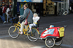 AMSTERDAM - NETHERLANDS - 19 OCTOBER 2004 -- Bicycles are famously the most popular mean of transportation in the city. A woman with one child sitting behind her while towing two children in a trailer. -- PHOTO:  EUP-IMAGES / JUHA ROININEN