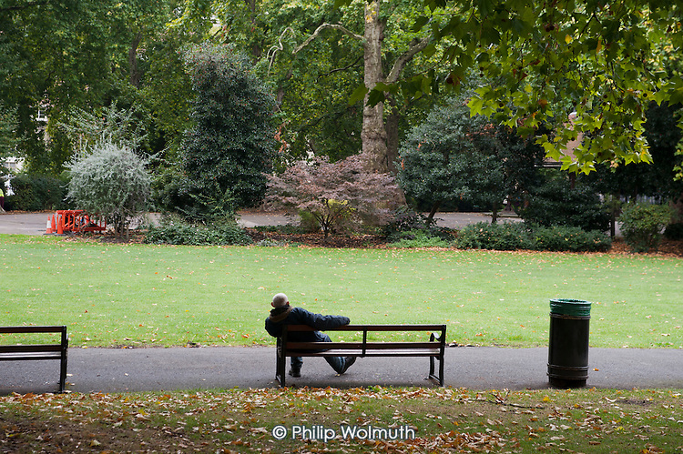 A man sits on a park bench in Lincoln's Inn Fields, London