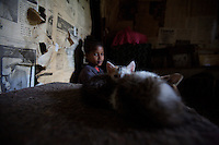 Tigist, 10 years old, one of two sisters living with HIV,  watches her kittens in the shack where she lives with her aunt, on a public hospital property in Addis Ababa, Ethiopia on Friday July 12 2006.. Ethiopia is one of the countries most affected by HIV/AIDS. Of its population of 77 million, three million are HIV-positive, according to government statistics. Every day sees 1,000 new infections. A million children under 14 have lost one or both parents to AIDS, and 200,000 children are living with AIDS. That makes Ethiopia the country with the most HIV-positive children.