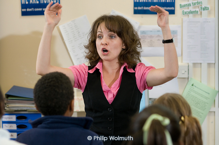 Music teacher Anna leads a Year 6 singing lesson, St Mary and St Michael Primary School, Stepney, Tower Hamlets, London