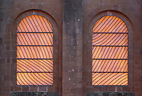 Stained glass windows by Pierre Soulages, 1987-94, seen from the exterior of the North transept, in the Abbatiale Sainte-Foy de Conques or Abbey-church of Saint-Foy, Conques, Aveyron, Midi-Pyrenees, France, a Romanesque abbey church begun 1050 under abbot Odolric to house the remains of St Foy, a 4th century female martyr. The glass used by Soulages is colourless and translucent, diffusing the light from outside without influencing the natural colours of the stone inside. The church is on the pilgrimage route to Santiago da Compostela, and is listed as a historic monument and a UNESCO World Heritage Site. Picture by Manuel Cohen