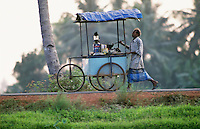 A man wheels his refreshment cart along the river bank in the Backwaters, Kerala.