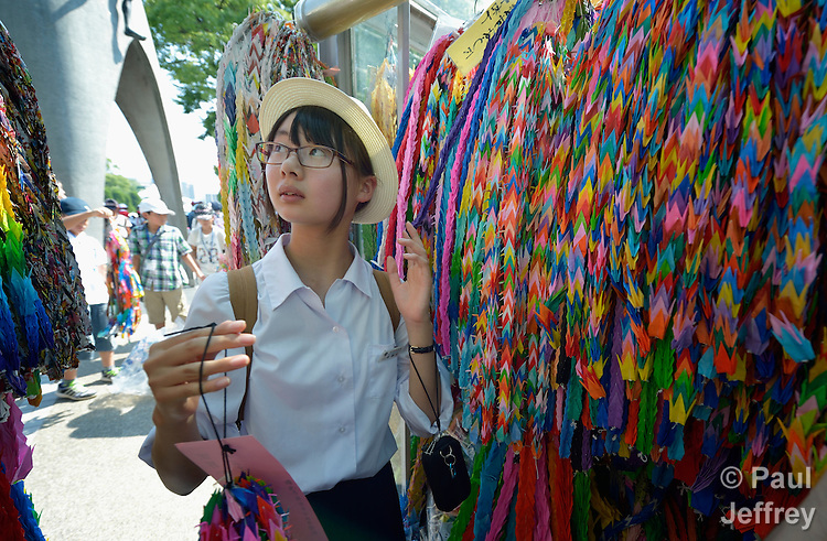 A girl deposits folded paper cranes she has brought to Hiroshima in commemoration of the 70th anniversary of the U.S. dropping an atomic bomb on the Japanese city of Hiroshima. The cranes are a sign of hope and peace.
