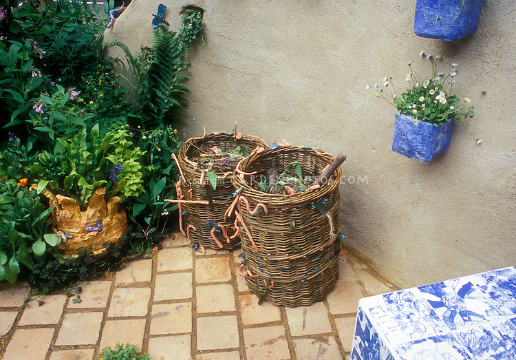 Two woven wicker compost bins on stone patio next to wall, garden plants, table