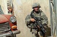 A member of the 82nd Airborne guarding a street corner near the new Baghdad market place draws curiosity from a local woman. (James J. Lee / Army Times