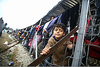 Pictured: A young boy at the Idomeni camp Monday 29 February 2016<br /> Re: A crowd of migrants has burst through a barbed-wire fence on the FYRO Macedonia-Greece border using a steel pole as a battering ram.<br /> TV footage showed migrants pushing against the fence at Idomeni, ripping away barbed wire, as FYRO Macedonian police let off tear gas to force them away.<br /> A section of fence was smashed open with the battering ram. It is not clear how many migrants got through.<br /> Many of those trying to reach northern Europe are Syrian and Iraqi refugees.<br /> About 6,500 people are stuck on the Greek side of the border, as FYRO Macedonia is letting very few in. Many have been camping in squalid conditions for a week or more, with little food or medical help.