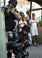 Students past by Brazil's police taking position during an operation against gangs of drug traffickers in the Complexo de Alemao slum in Rio de Janeiro, Brazil, June 13, 2007.  Rio de Janeiro is one of Brazil's most violence-plagued cities with an annual homicide rate of around 50 per 100,000 residents. (FOTO:GILBERTO MENDES/.AUSTRAL FOTO)