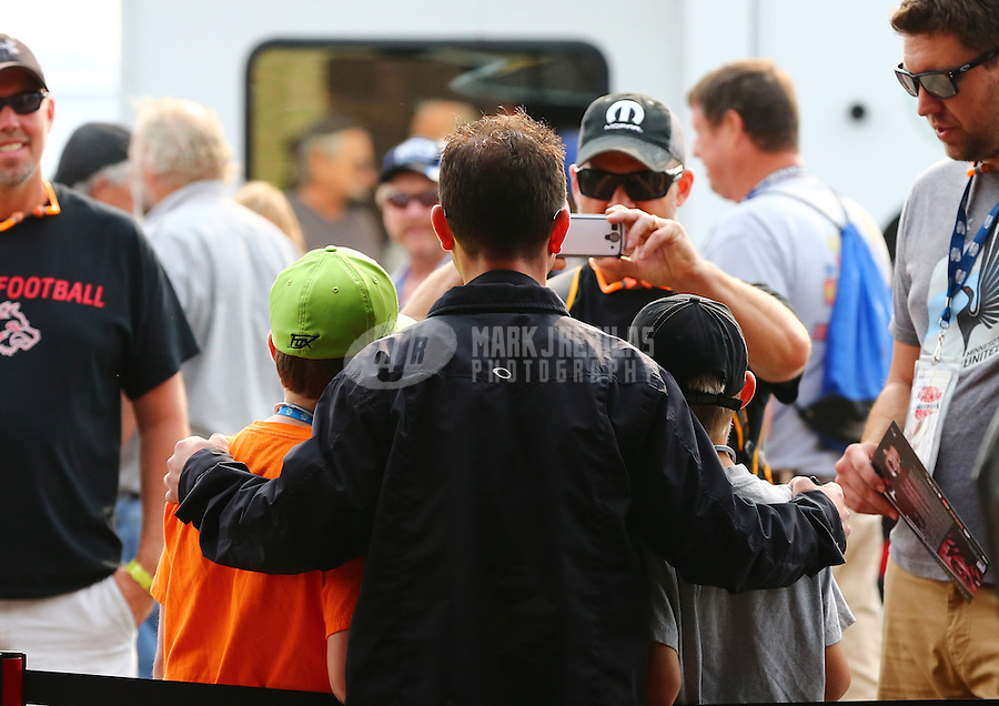 Aug. 18, 2013; Brainerd, MN, USA: NHRA top fuel dragster driver Steve Torrence poses with some young fans during the Lucas Oil Nationals at Brainerd International Raceway. Mandatory Credit: Mark J. Rebilas-