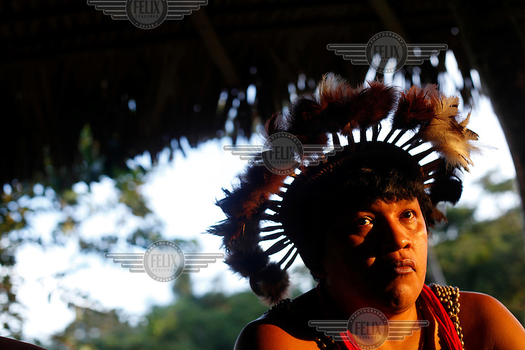 Almir Narayamoga (the one who unites) Surui, chief of the Surui (Paiter) tribe at a meeting of tribal leaders in the village of Lapetanha, in the Brazilian Amazon. He is a warrior of the Gabgirey (black wasp) clan. The meeting was arranged to discuss projects such as reforestation and tourism. Almir, sporting tribal body paintings, has vowed to save the Surui, the Amazon, and the world through reforesting the jungle.  He has teamed up with Google and uses technology, such as laptops and smart phones in his campaigns. The Surui had had no contact with the world outside their Amazonian homelands until, in 1969, a road was built through their territory. At the time there were around 5000 Surui but within three years disease had wiped out all but 290 Surui.