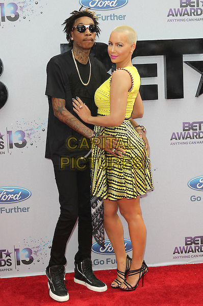 Wiz Khalifa, Amber Rose<br /> 2013 BET Awards held at Nokia Theatre L.A. Live, Los Angeles, California, USA.<br /> June 30th, 2013<br /> full length black shirt jeans denim yellow dress couple sunglasses shades couple crochet tattoos side looking over shoulder <br /> CAP/ADM/KB<br /> &copy;Kevan Brooks/AdMedia/Capital Pictures